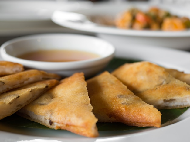 Chiuda su del rotolo di molla croccante farcito con i gamberetti e la carne di maiale su un piatto bianco in un ristorante