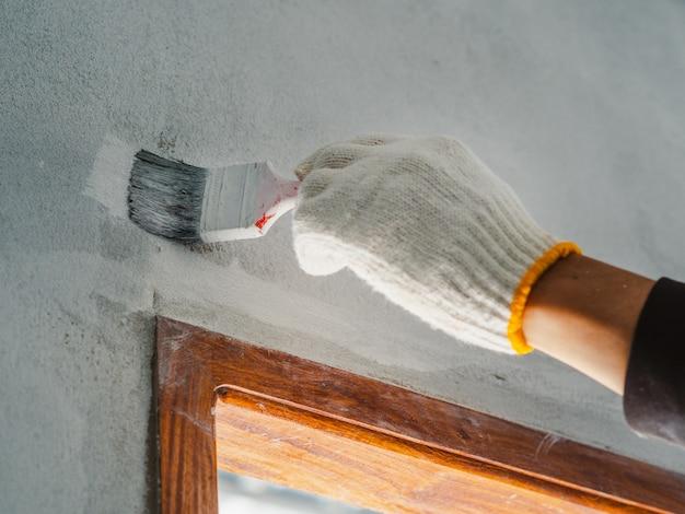 Chiuda su del rullo e della spazzola di uso della mano del lavoratore per la parete della pittura. concetto di costruzione di casa.