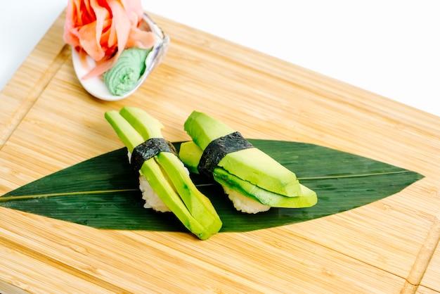 Chiuda su del sashimi dell'avocado servito con lo zenzero e il wasabi sul bordo di legno