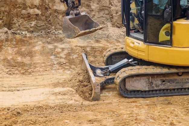 Chiuda su del suolo commovente della paletta del bulldozer per il cantiere della costruzione di fondazione,