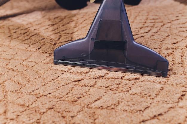 Chiuda su del tappeto di pulizia dell'ugello dell'aspirapolvere a casa.