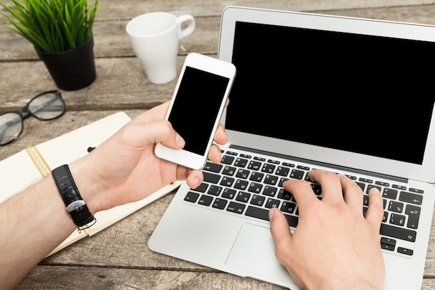 Chiuda su del tipo dei pantaloni a vita bassa che manda un sms con il suo smartphone in ufficio