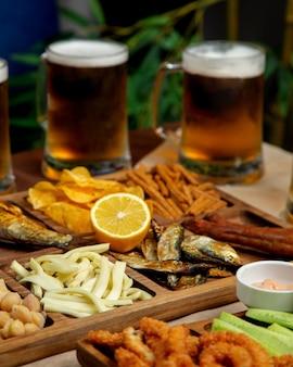 Chiuda su del vassoio degli spuntini della birra con le patatine fritte dei ceci delle aringhe affumicate del formaggio di stringa