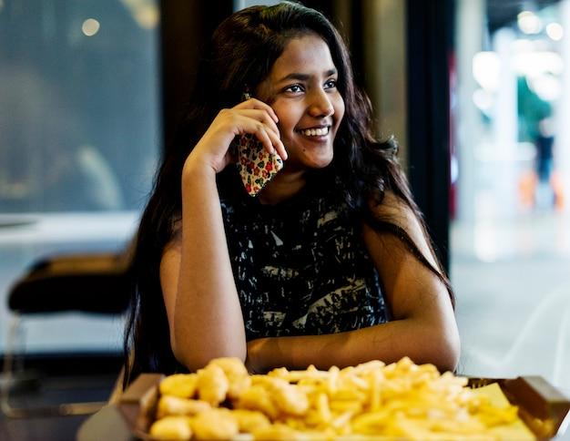 Chiuda su dell'adolescente che parla su un telefono che mangia il concetto della cultura della gioventù delle patate fritte