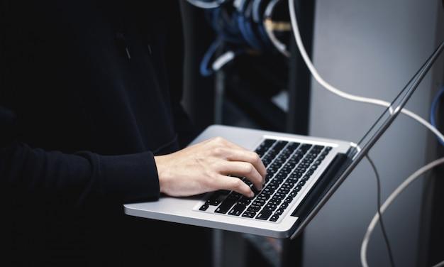 Chiuda su dell'amministratore delle mani che lavora al computer portatile nel centro dati