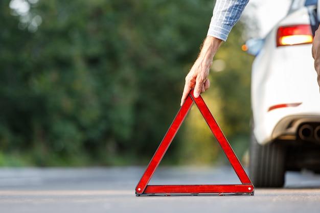 Chiuda su dell'autista dell'uomo che mette il triangolo d'avvertimento rosso / segno di arresto di emergenza dietro la sua automobile rotta dal lato della strada