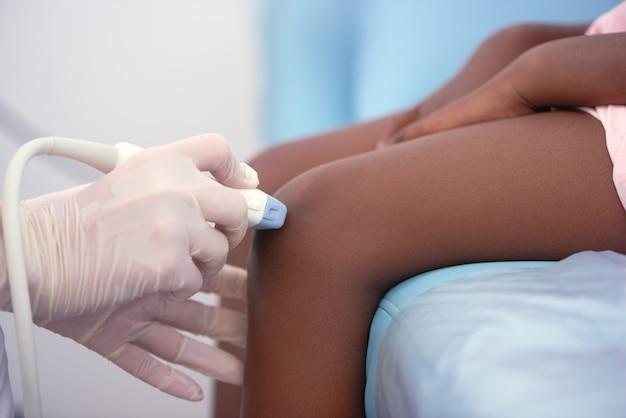 Chiuda su dell'ultrasuono dell'articolazione del ginocchio del bambino afro all'ospedale.