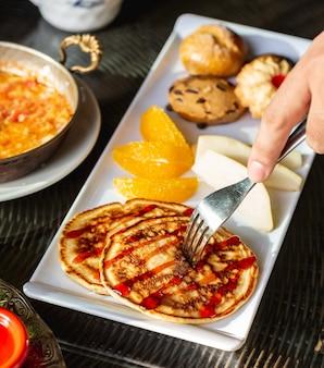 Chiuda su dell'uomo che prende il piccolo pancake con lo sciroppo di fragole