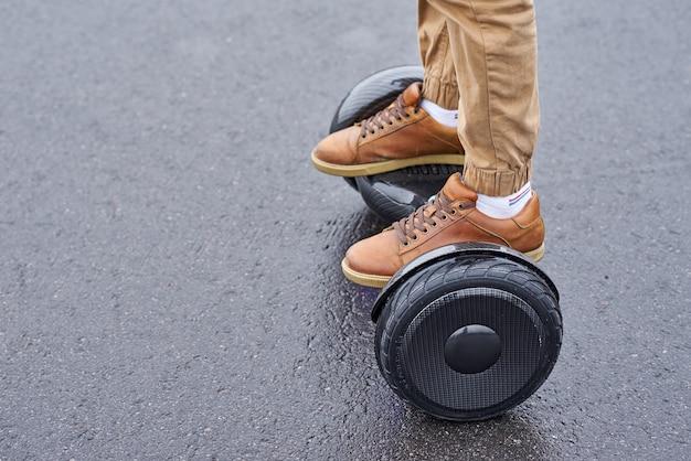 Chiuda su dell'uomo che usando hoverboard sulla strada asfaltata