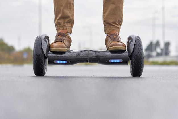 Chiuda su dell'uomo che usando il hoverboard sulla strada asfaltata.