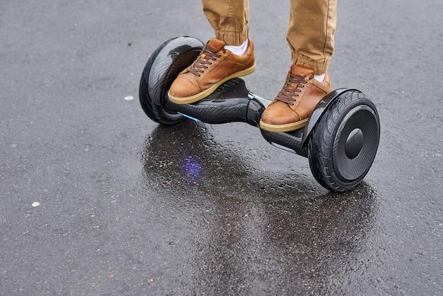 Chiuda su dell'uomo che usando la strada asfaltata del hoverboard, i piedi sul motorino elettrico all'aperto