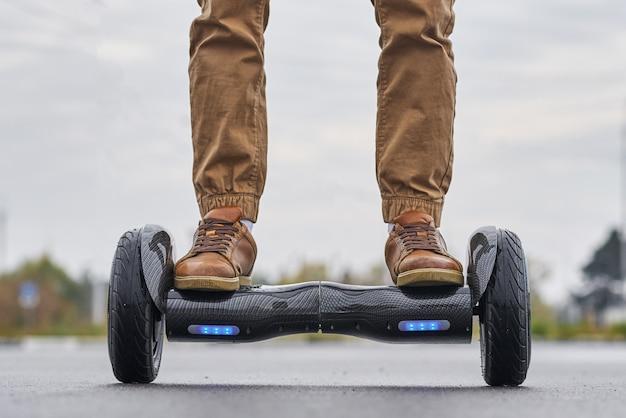 Chiuda su dell'uomo che usando la strada asfaltata di hoverboard, i piedi sul motorino elettrico all'aperto, vista frontale