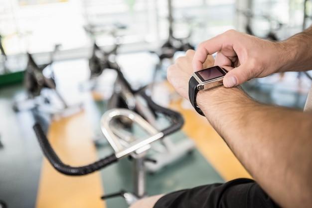 Chiuda su dell'uomo che usando lo smartwatch sulla bici di esercizio in palestra