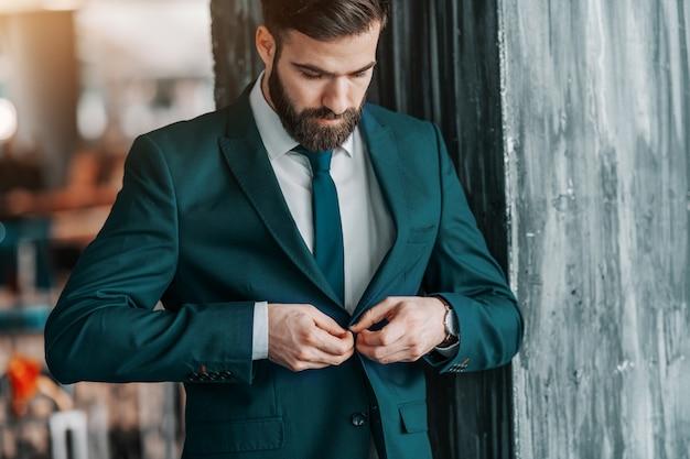 Chiuda su dell'uomo d'affari caucasico bello che abbottona il rivestimento mentre sta all'aperto.