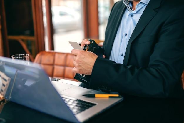 Chiuda su dell'uomo d'affari senior che prende il carretto di credito dal portafoglio mentre si siedono nel self-service.