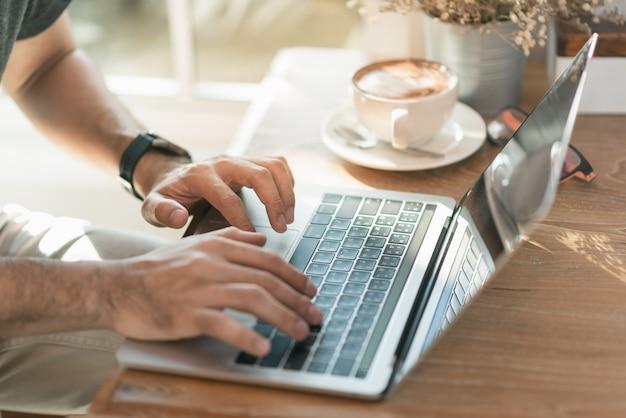 Chiuda su dell'uomo della mano che lavora con il computer portatile e beva un caffè caldo nella caffetteria
