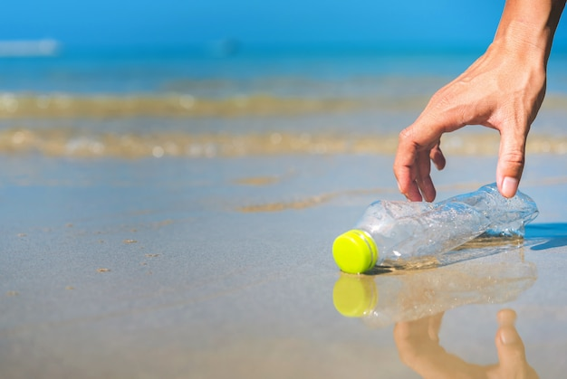 Chiuda su dell'uomo della mano che prende la pulizia della bottiglia di plastica sulla spiaggia