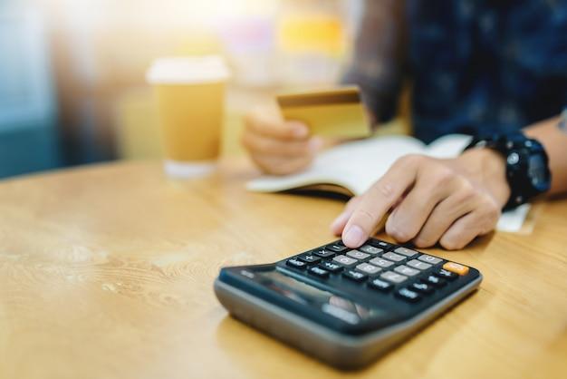 Chiuda su dell'uomo di affari che lavora con la mano di dati finanziari facendo uso del calcolatore al caffè del caffè.