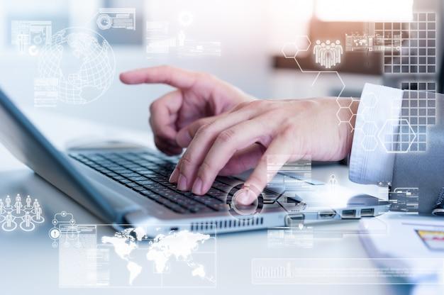 Chiuda su dell'uomo di affari che scrive sul computer portatile con effetto di strato della tecnologia