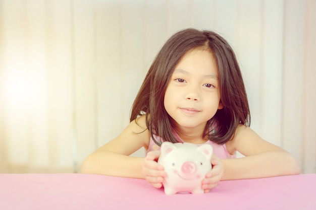 Chiuda su della bambina sveglia con il porcellino salvadanaio, concetto di risparmio del bambino.