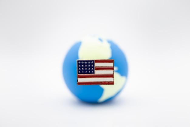 Chiuda su della bandiera nazionale del perno dello stato unito d'america sopra la mini palla del mondo su bianco
