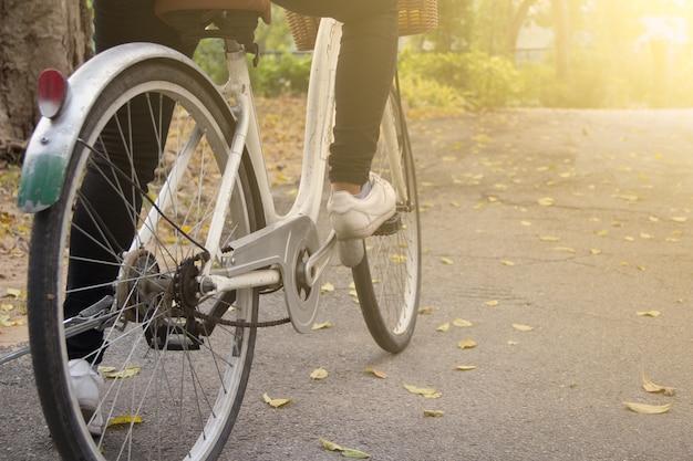 Chiuda su della bicicletta di guida della giovane donna in parco