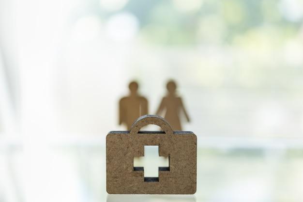Chiuda su della borsa di legno di medico con l'icona trasversale sulla tavola con il modello della donna e dell'uomo nel blackground con lo spazio della copia.