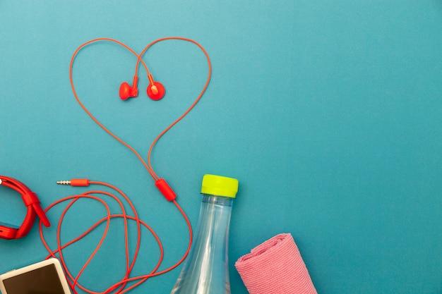 Chiuda su della bottiglia di acqua, dell'orologio e dei trasduttori auricolari rossi simbolo del cuore su fondo di carta