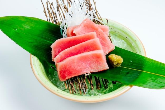 Chiuda su della ciotola del sashimi di tonno servita sul bordo del bastone nel fondo bianco