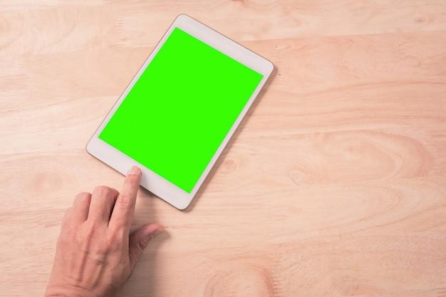 Chiuda su della compressa dello smart phone di tocco della mano con lo schermo verde su legno
