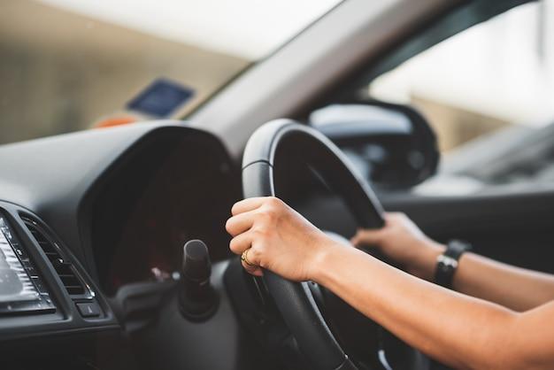 Chiuda su della donna che conduce un'automobile sulla strada - concetto del trasporto