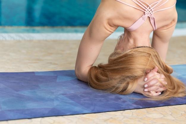 Chiuda su della donna che fa le pose di yoga, gesto di mani vicino alla piscina