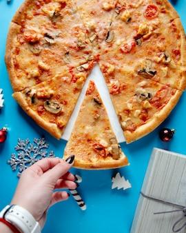 Chiuda su della donna che prende una fetta di pizza con il pomodoro e il formaggio del pollo del fungo