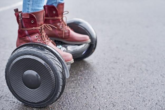 Chiuda su della donna che usando la strada asfaltata del hoverboard, i piedi sul motorino elettrico all'aperto