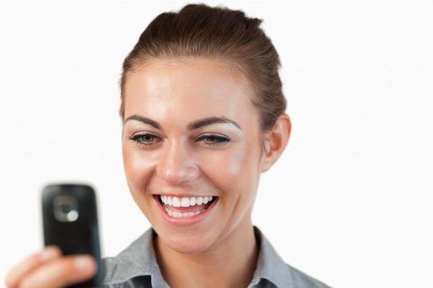 Chiuda su della donna di affari che è felice circa il messaggio di testo