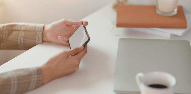 Chiuda su della donna di affari che si rilassa mentre tengono lo smartphone orizzontale dello schermo in bianco nella stanza dell'ufficio