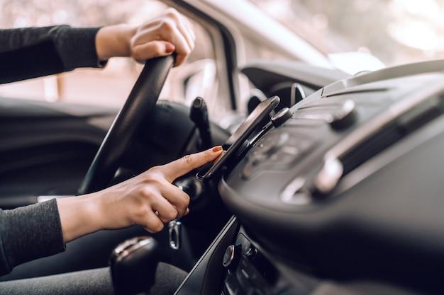 Chiuda su della donna incinta caucasica che conduce l'automobile e che accende i gps sullo smart phone.