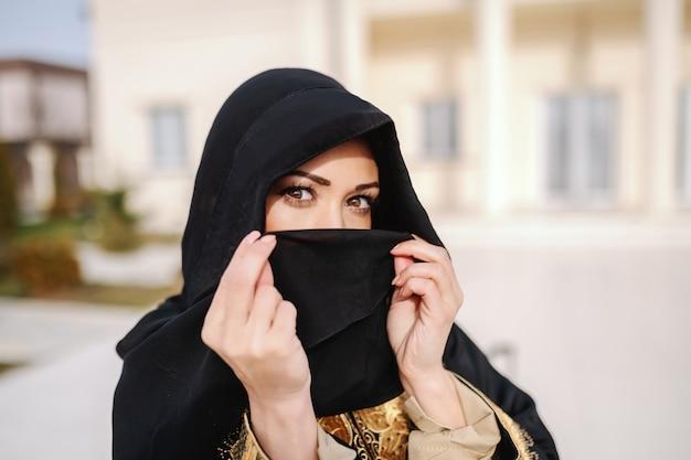 Chiuda su della donna musulmana splendida che copre il suo fronte di sciarpa mentre sta all'aperto.