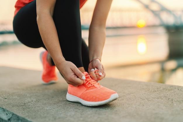 Chiuda su della donna sportiva che lega il laccetto mentre si inginocchia all'aperto, in ponte del fondo. concetto di fitness all'aperto.