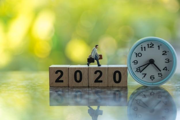 Chiuda su della figura miniatura dell'uomo d'affari con la borsa che funziona sul blocchetto di numero di legno 2020 con l'orologio rotondo e la natura verde della foglia.