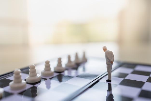 Chiuda su della figura miniatura della gente dell'uomo d'affari che sta sulla scacchiera con i pezzi degli scacchi del pegno e copi lo spazio.