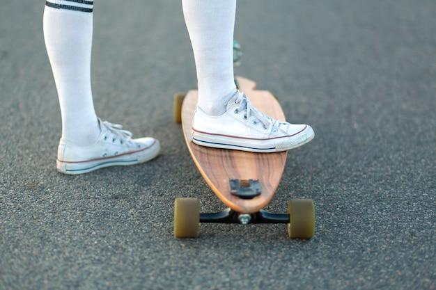 Chiuda su della gamba di signora in scarpe da tennis bianche che riposano dopo il giro divertente estremo il suo pattino di legno di longboard, la ragazza moderna dei pantaloni a vita bassa urbana si diverte