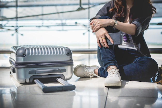 Chiuda su della giovane donna con i bagagli della valigia e della borsa che aspettano la partenza