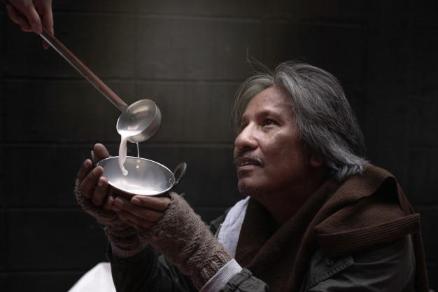 Chiuda su della mano asiatica di vagabondo o del senzatetto che tiene una tazza e ritenga felice con il cibo donato
