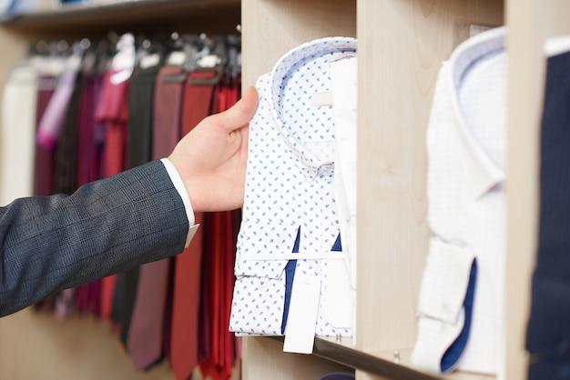 Chiuda su della mano dell'uomo che tiene la camicia bianca nel modello blu.