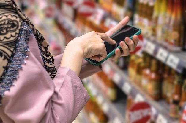 Chiuda su della mano della donna facendo uso dello smartphone nell'acquisto al supermercato