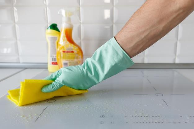 Chiuda su della mano della donna in guanti di gomma protettivi che lavano o che puliscono la fresa bianca moderna di induzione da uno straccio nella cucina, prodotti di pulizia vaghi