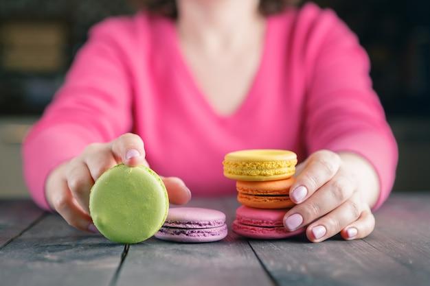 Chiuda su della mano femminile della pasticceria che cucina il macaron delizioso