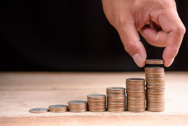 Chiuda su della mano maschio che impila le monete, la finanza di affari ed il concetto dei soldi, risparmiano i soldi per preparano in t