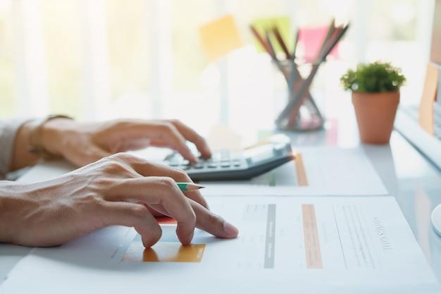Chiuda su della penna di tenuta della mano del ragioniere o dell'uomo d'affari che lavora al calcolatore per calcolare i dati di gestione